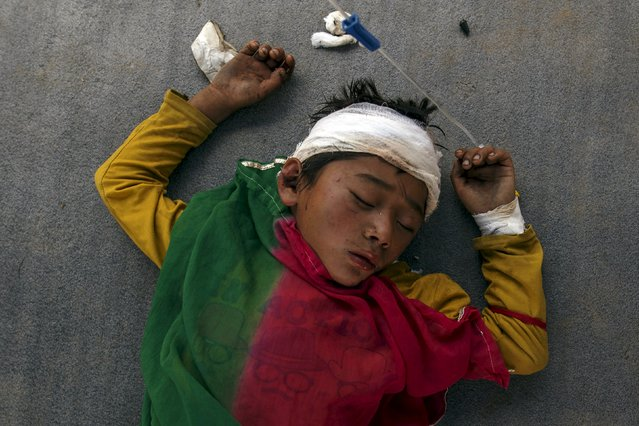 An injured boy sleeps on the ground outside the overcrowded Dhading hospital, in the aftermath of Saturday's earthquake, in Dhading Besi, Nepal April 27, 2015. (Photo by Athit Perawongmetha/Reuters)