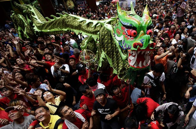 Revelers try to catch cash envelopes and other items being given away following a dragon and lion performance in front of a grocery store in celebration of the Chinese New Year in Manila's Chinatown district. (Photo by Bullit Marquez/Associated Press)