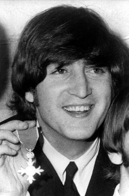Beatle John Lennon smiles as he poses with his Member of the Order of the British Empire medal (MBE), presented to the Beatles by the Queen of England in a ceremony at Buckingham Palace, in London, England on October 26, 1965. (Photo by AP Photo)