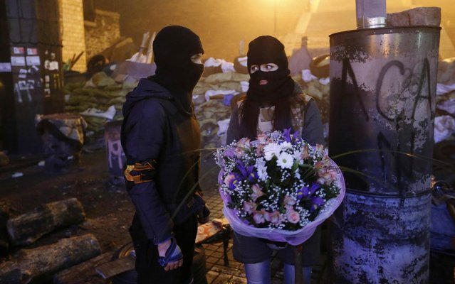 "An activist from the ""Right Sector"" anti-government protest group presents a bouquet of flowers to his girlfriend in front of fellow activists near the site of previous clashes with riot police in Kiev, February 13, 2014. (Photo by Reuters/Stringer)"