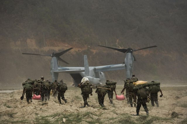 Nepalese soldiers prepare to board one of U.S. Ospreys which is used to deploy them in the quake affected mountainous areas in Manthali, Nepal, Thursday, May 7, 2015. The April 25 earthquake killed thousands and injured many more as it flattened mountain villages and destroyed buildings and archaeological sites in Kathmandu. (Photo by Bernat Amangue/AP Photo)