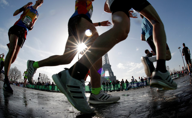 Runners make their way past the Eiffel Tower as they participate in the 42nd Paris Marathon, in France, April 8, 2018. (Photo by Philippe Wojazer/Reuters)