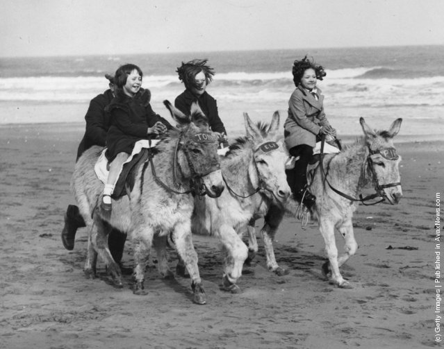 Three young girls enjoy one of the first rides of the donkey season on the beach, 1934