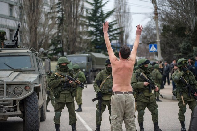 A Ukrainian man stands in protest in front of gunmen in unmarked uniforms as they stand guard in Balaklava, on the outskirts of Sevastopol, Ukraine, Saturday, March 1, 2014. (Photo by Andrew Lubimov/AP Photo)