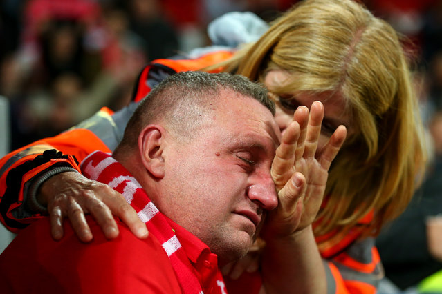 A tearful fan of Liverpool is consoled by a steward at full time during the UEFA Champions League Semi Final second leg match between Liverpool and Barcelona at Anfield on May 7, 2019 in Liverpool, England. (Photo by Robbie Jay Barratt – AMA/Getty Images)