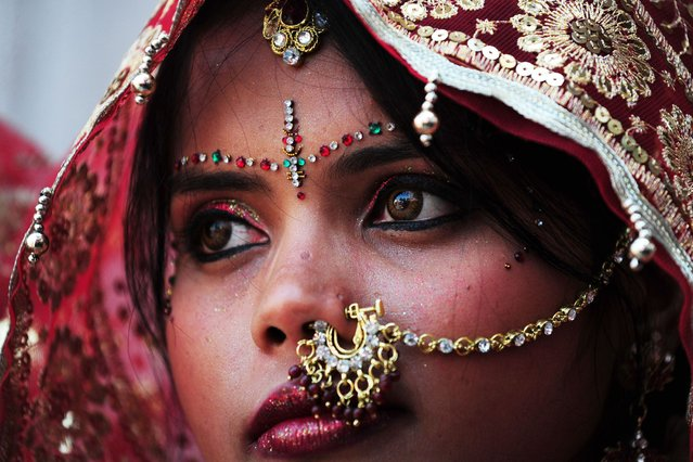 An Indian bride looks on as she and ten other women waiting to marry wait for their grooms to arrive at their wedding ceremony at a local Hindu temple in New Delhi on March 3, 2014. Eleven couples tied the knot at the same time. (Photo by Roberto Schmidt/AFP Photo)
