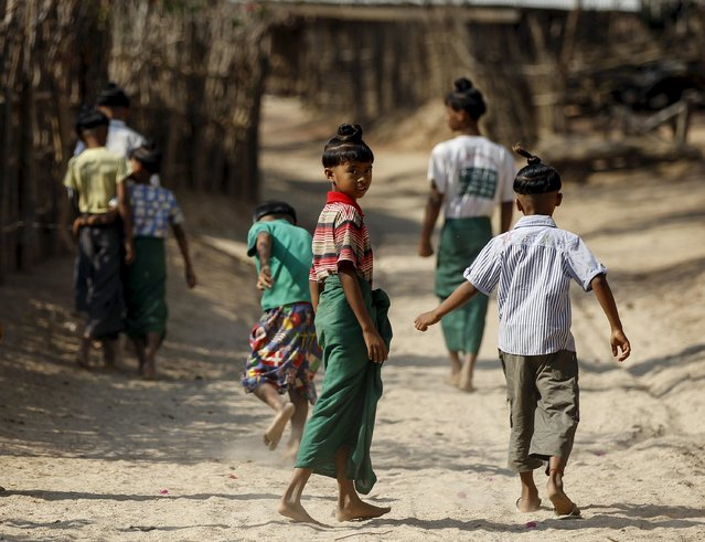 That Naing Oo (C), 11, and others boys sporting the ancient hairstyle known as Sanyitwine walk down a road at Sat Sat Yo village in Nyaung Oo township, near Myanmar's ancient city Bagan April 17, 2015. (Photo by Soe Zeya Tun/Reuters)