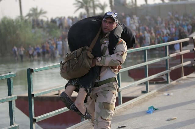 An Iraqi soldier carries a displaced woman to help her cross the bridge at the outskirts of Baghdad May 19, 2015. Iraqi security forces on Tuesday deployed tanks and artillery around Ramadi to confront Islamic State fighters who have captured the city in a major defeat for the Baghdad government and its Western backers. (Photo by Reuters/Stringer)