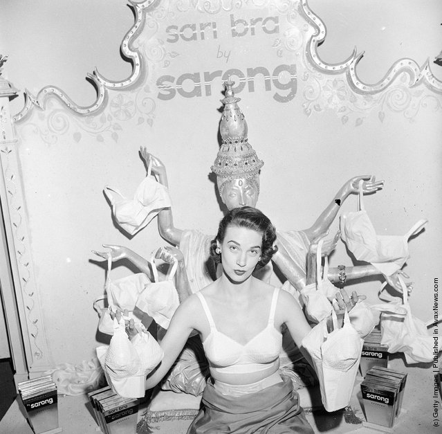 1949: A woman modelling a 'Sarong' brand sari bra whilst holding one on in each of her outstretched hands