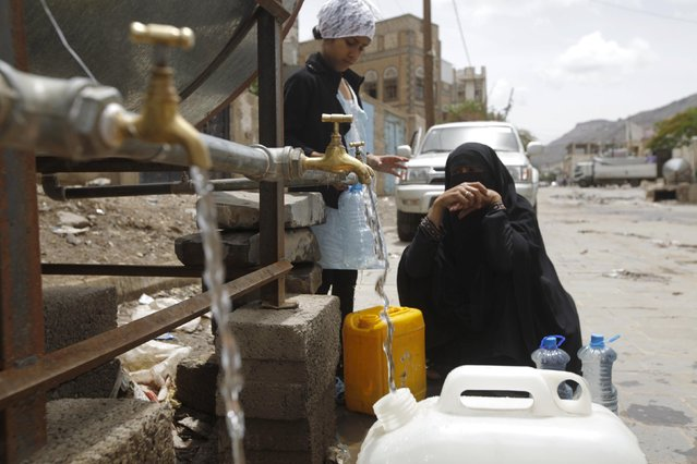 A woman fills jerrycans with clean water from a donated source amid a shortage of water supplies, in Yemen's capital Sanaa, April 14, 2016. (Photo by Mohamed al-Sayaghi/Reuters)