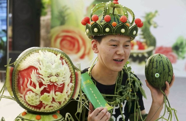 A man wearing a headpiece made of watermelon peel stands next to a watermelon sculpture during an annual watermelon festival in Daxing district, Beijing, China, May 25, 2015. (Photo by Reuters/China Daily)