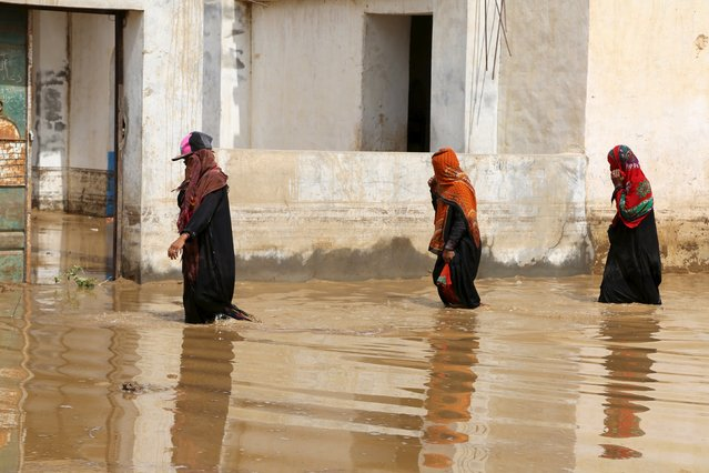 Women wade through a flooded street following heavy rain in a village in Yemen's Red Sea province of Houdieda April 15, 2016. (Photo by Abduljabbar Zeyad/Reuters)