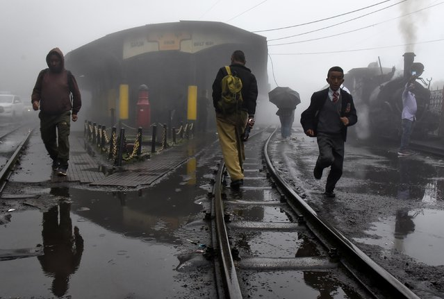 People cross tracks as a Darjeeling Himalayan Railway train, which runs on a 2 foot gauge railway and is a UNESCO World Heritage Site, prepares to depart from a station in Ghum, India, June 25, 2019. (Photo by Ranita Roy/Reuters)