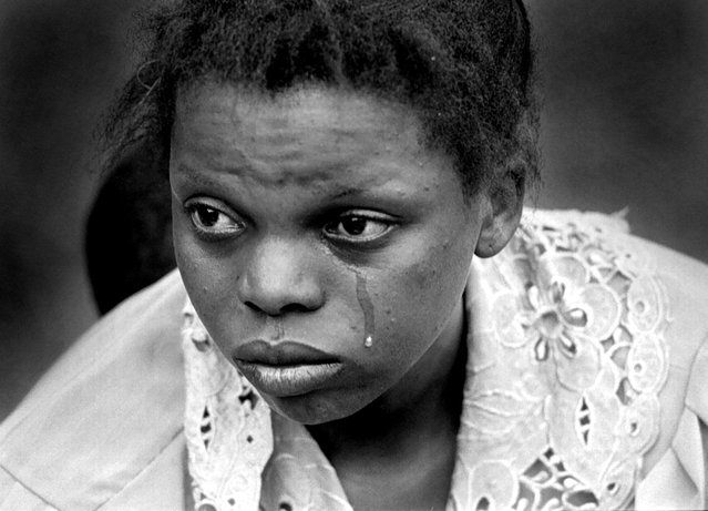 A woman cries with exhaustion after she was unable to get on a truck to Kigali, Rwanda; 1996. (Photo by Carol Guzy/The Washington Post)