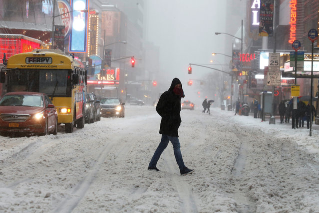 A commuter walks across a street during a snowstorm in Times Square in Manhattan, New York, U.S., March 14, 2017. (Photo by Carlo Allegri/Reuters)
