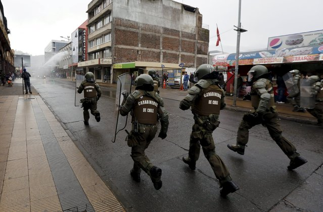 Riot police run to control a students' demonstration for education reform, in Temuco June 25, 2015. (Photo by Mariana Bazo/Reuters)