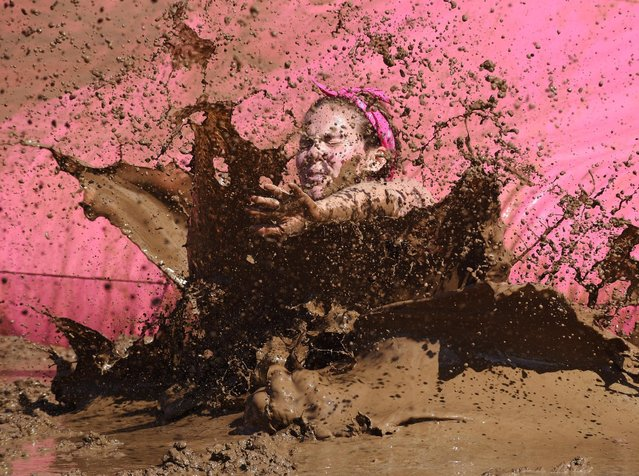 Danielle McKenna of Volo, Ill., splashes down during the Dirty Girl Mud Run at the Sears Centre in Hoffman Estates, Ill., on Saturday, June 27, 2015. (Photo by Joe Lewnard/Daily Herald via AP Photo)