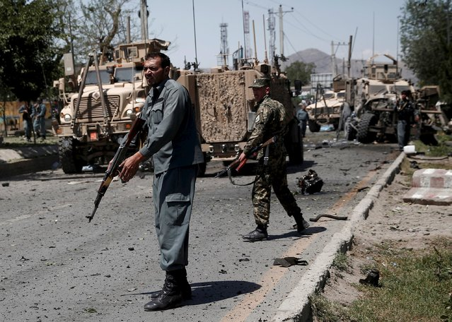 Afghan policemen stand at the site of a suicide bomb attack in Kabul, Afghanistan June 30, 2015. (Photo by Ahmad Masood/Reuters)