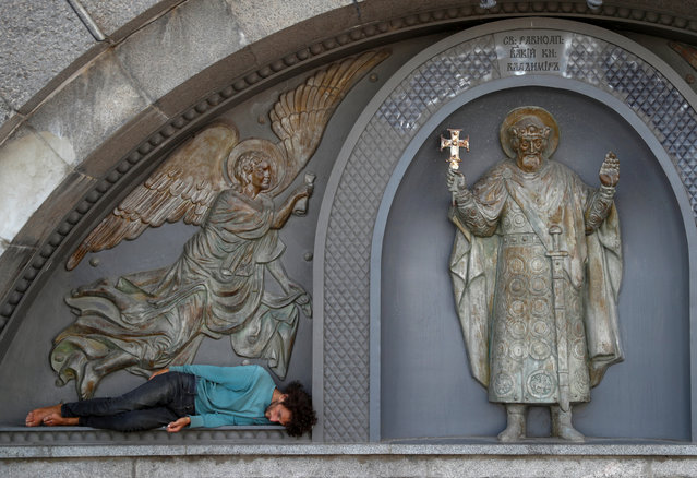A man rests near a sculpture of Saint Volodymyr, part of the bas-relief of an embankment of the Dnipro River, in Kiev, Ukraine on August 14, 2019. (Photo by Valentyn Ogirenko/Reuters)