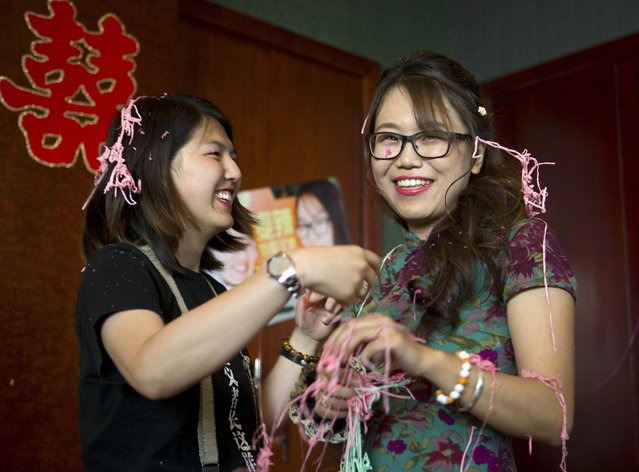 Li Tingting, left, and Teresa Xu, right, clean silly string off of each other after being sprayed by a well-wisher at their wedding in Beijing, Thursday, July 2, 2015. (Photo by Mark Schiefelbein/AP Photo)
