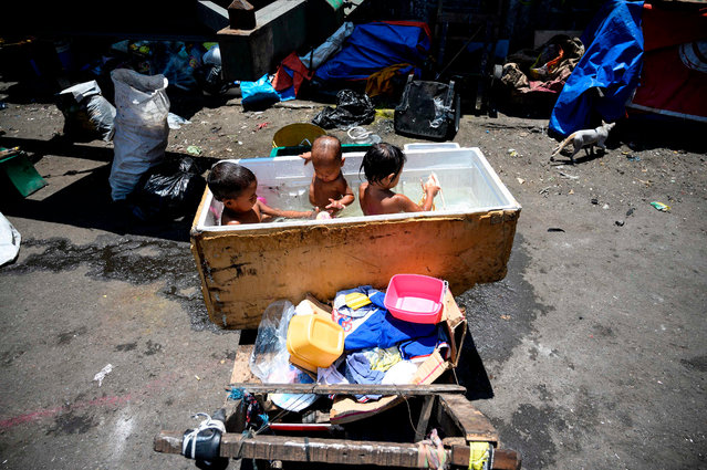 Children bathe in a makeshift tub from a discarded refrigerator in Manila on June 9, 2019. (Photo by Noel Celis/AFP Photo)