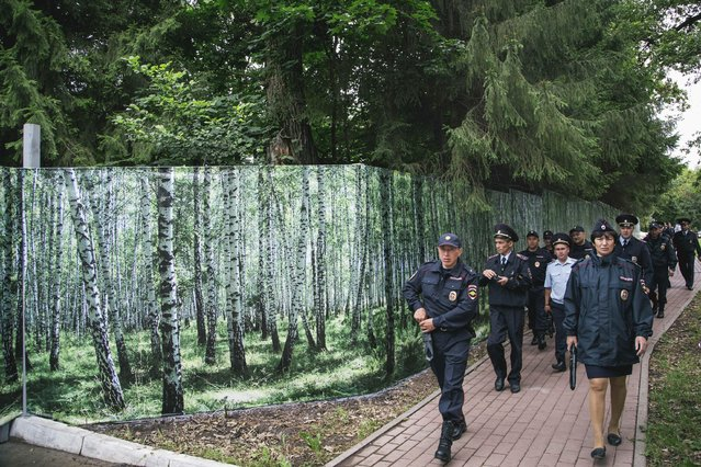In this photo taken on Sunday, July  5, 2015, police officers walk along a giant poster to give an improved appearance, in downtown Ufa, Russia. Ufa will host SOC (Shanghai Cooperation Organization) and BRICS (Brazil, Russia, India, China and South Africa) summits July 7 to July 9, 2015. (Photo by Vadim Braydov/AP Photo)