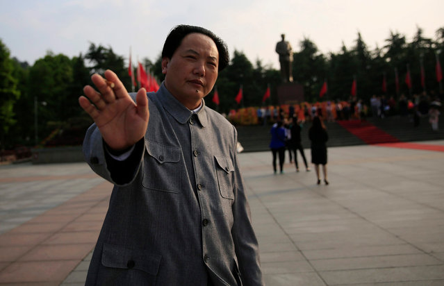 A Chairman Mao look-alike actor gestures to stop the photographer from taking his photo on the Mao Zedong Bronze Statue Square in Shaoshan, Hunan Province in central China, 27 April 2016. (Photo by How Hwee Young/EPA)
