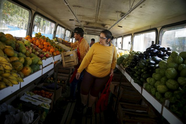 A woman looks for fruits to buy inside a bus called Sacolao in Santa Teresa neighborhood in Rio de Janeiro, Brazil, July 7, 2015. (Photo by Pilar Olivares/Reuters)