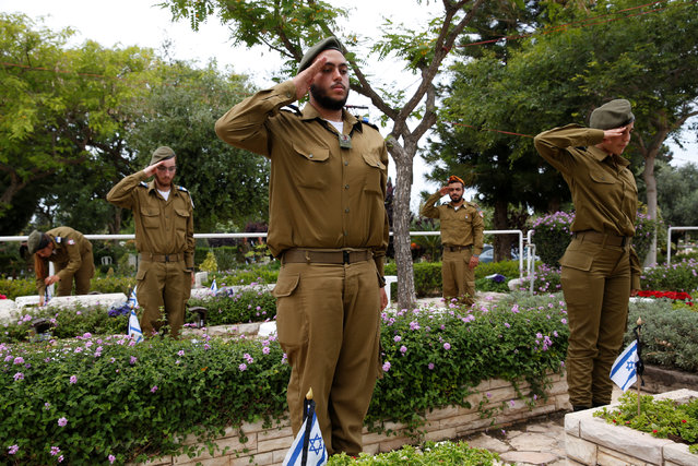 Israeli soldiers salute as they stand next to graves of fallen soldiers during a ceremony ahead of Memorial Day, commemorating those who died during conflicts, at the Kiryat Shaul military cemetery in Tel Aviv, Israel May 10, 2016. (Photo by Baz Ratner/Reuters)