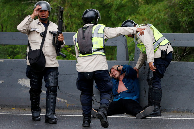 Riot policemen help an injured protester during a rally to demand a referendum to remove President Nicolas Maduro in Caracas, Venezuela, May 11, 2016. (Photo by Carlos Garcia Rawlins/Reuters)