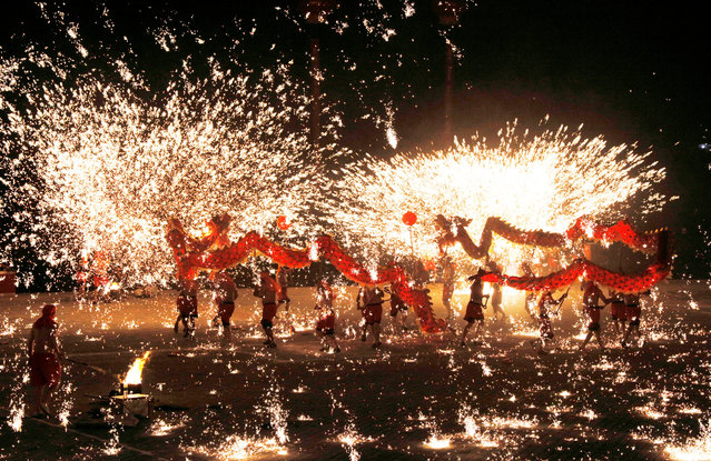 Artists perform a fire dragon dance under a shower of sparks from molten iron in Huaying, Sichuan province, China May 1, 2016. (Photo by Reuters/Stringer)