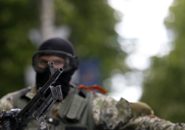 A pro-Russian gunman atop a car patrols through the center of Slovyansk, eastern Ukraine, Thursday, May 8, 2014. A strong majority of Ukrainians want their country to remain a single, unified state and this is true even in the largely Russian-speaking east where a pro-Russia insurgency has been fighting for autonomy, a poll released Thursday shows. (Photo by Darko Vojinovic/AP Photo)