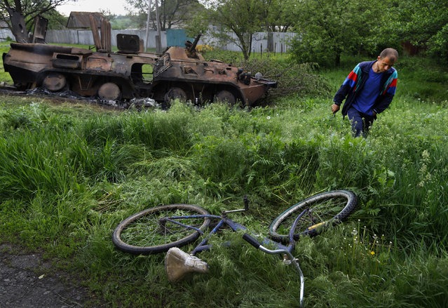 A local walks by a destroyed Ukrainian army Armoured Personnel Carrier in the eastern Ukrainian village of Oktyabrskoe May 14, 2014. Pro-Russian separatists ambushed Ukrainian troops on May 13, killing seven in the heaviest loss of life for government forces in a single clash since Kiev sent soldiers to put down a rebellion in the country's east. (Photo by Yannis Behrakis/Reuters)