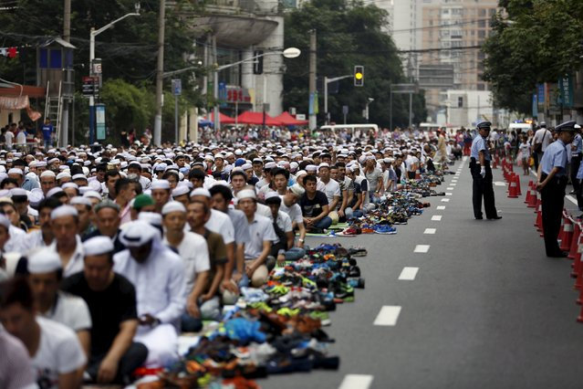 Muslims attend a prayer session on a street near a mosque on Eid al-Fitr, in Shanghai, July 18, 2015. The Eid al-Fitr festival marks the end of the holy Muslim fasting month of Ramadan. (Photo by Aly Song/Reuters)