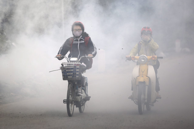 People ride past smokes created by burning waste materials in the street, in Hanoi, Vietnam 07 March 2016. Reports said air pollution rate in Hanoi had recently recorded hazardous level, which increases the risk of many diseases and endangers public health. (Photo by Luong Thai Linh/EPA)
