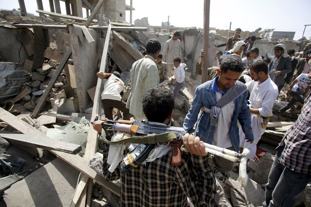 An armed Houthi militant (bottom C) watches as vendors and people salvage goods from under the rubble of shops destroyed by a Saudi-led air strike that hit a marketplace in Yemen's capital Sanaa July 20, 2015. Saudi-led coalition of Arab states has been bombing the Iranian-allied Houthi rebel movement and army forces loyal to former Yemeni president Ali Abdullah Saleh since late March in a bid to restore exiled President Abd-Rabbu Mansour Hadi to power. (Photo by Khaled Abdullah/Reuters)