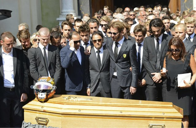 Formula One drivers Jean-Eric Vergne (4thR) and Felipe Massa (C), friends and relatives gather around the coffin of late Marussia F1 driver Jules Bianchi during the funeral ceremony at the Sainte Reparate Cathedral in Nice, France, July 21, 2015. Bianchi, 25, died in hospital in Nice on Friday, nine months after his crash at Suzuka in Japan and without regaining consciousness. (Photo by Jean-Pierre Amet/Reuters)
