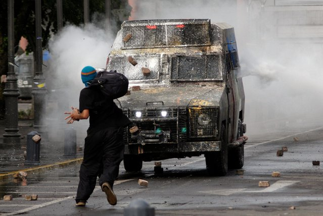 A demonstrator throws stones at a police vehicle during a protest against Chile's government in Concepcion, Chile on November 7, 2019. (Photo by Jose Luis Saavedra/Reuters)