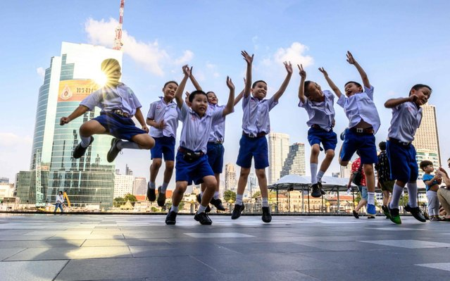 Schoolboys jump for a photo at a pier of the Chao Phraya river in Bangkok, Thailand on September 25, 2019. (Photo by Mladen Antonov/AFP Photo)
