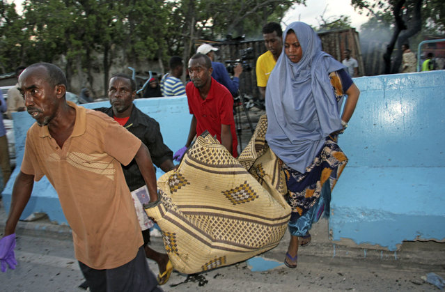 Somalis carry away the dead body of a person who was killed when a car bomb detonated in Mogadishu, Somalia, Wednesday, May 24, 2017. A Somali police officer says a number of people have been killed in a car bomb blast outside a restaurant near the port in the capital. (Photo by Farah Abdi Warsameh/AP Photo)