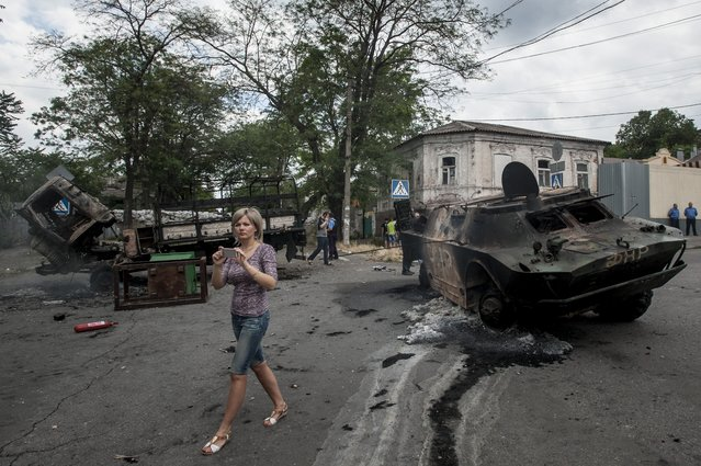 A local woman prepares to take pictures of a site of a battle  between Ukrainian troops and pro-Russian fighters in Mariupol, eastern Ukraine, Friday, June 13, 2014. Ukraine's interior minister says that government troops have attacked pro-Russian separatists in the southern port of Mariupol. Arsen Avakov said Friday that four government troops were wounded as forces retook buildings occupied by the rebels in the center of the town. (Photo by Evgeniy Maloletka/AP Photo)
