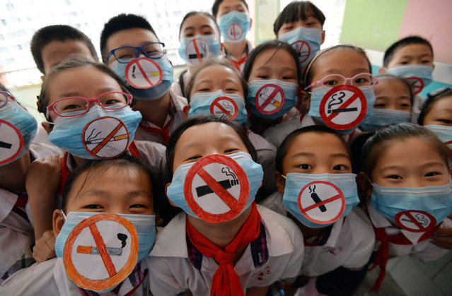 This photo taken on May 30, 2016 shows students wearing masks with no smoking signs to support World No Tobacco Day at a primary school in Handan, northern China's Hebei province. The slumping output of tobacco products in China has become one of the factors in the country's lowest industrial production rate since the global financial crisis during the first two months of the year. (Photo by AFP Photo/Stringer)