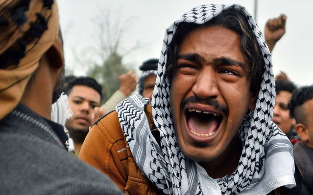 An Iraqi man mourns his brother during a funeral procession for anti-government demonstrators killed during protests a day earlier, in the central holy shrine city of Najaf on November 29, 2019. Nearly 45 people were reportedly killed and hundreds wounded across Iraq yesterday, at least 16 of them in Najaf, a day after the torching of Iran's consulate there. (Photo by Haidar Hamdani/AFP Photo)