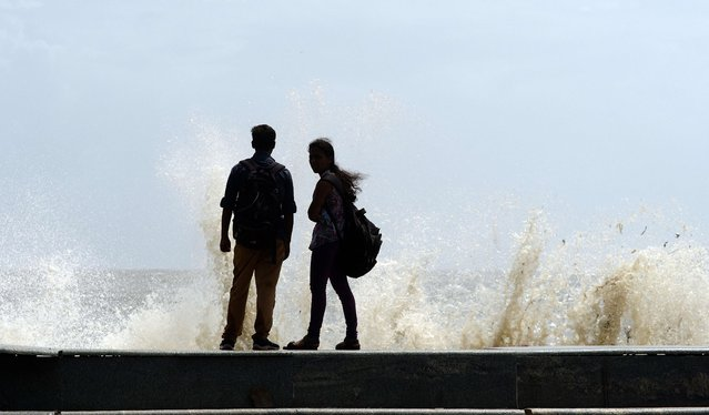 "Onlookers stand on the promenade at Marine Drive as sea waves lash the shore during high tide in Mumbai on June 12, 2014. The India Meteorological Department (IMD) having declared the onset of the monsoon, has predicted below average rains with a 23 percent chance of a ""deficient monsoon"". The monsoon season, which runs from June to September, accounts for about 80 percent of India's annual rainfall, vital for a farm economy which lacks adequate irrigation facilities. (Photo by Indranil Mukherjee/AFP Photo)"