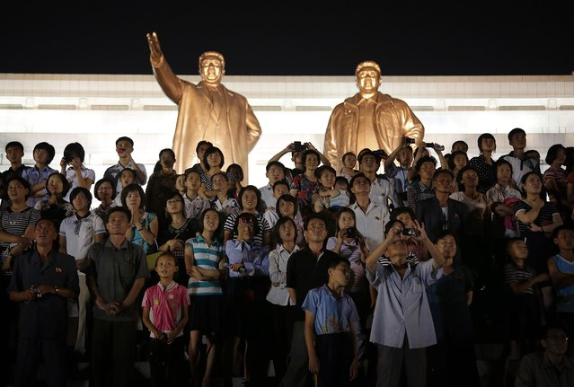 The bronze statues of the late North Korean leaders Kim Il Sung and Kim Jong Il tower over people as they watch fireworks explode, Monday, July 27, 2015, in Pyongyang, North Korea as part of celebrations for the 62nd anniversary of the armistice that ended the Korean War. (Photo by Wong Maye-E/AP Photo)