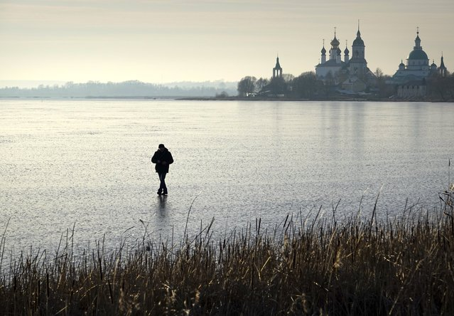 A man walks on frozen Nero lake, outside old Russian city Rostov Veliky (Rostov the Great), a town in Yaroslavl Oblast, about 200 kilometers (125 miles) south-east of Moscow, Russia, Saturday, November 23, 2019. The temperature in Yaroslavl region dropped down to -6 degree Celsius (21,2 degree Fahrenheit). (Photo by Dmitry Kozlov/AP Photo)