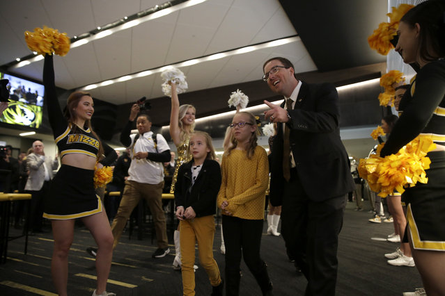 Eliah Drinkwitz walks to the stage to be introduced as the new NCAA college football head coach at the University of Missouri, with his children Emerson, 6, left, and Addison, 9, Tuesday, December 10, 2019, in Columbia, Mo. Drinkwitz becomes the 33rd head football coach at Missouri after coaching the 2019 season at Appalachian State. (Photo by Jeff Roberson/AP Photo)