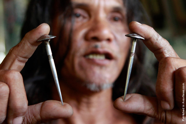 Penitent Ruben Eniaje holds up two of the custom-made three-inch stainless steel nails that will be used for his crucifixion on Good Friday in Cutud, San Fernando Pampanga, in northern Philippines on April 21, 2011. Dozens of penitents were crucified on wooden crosses on Good Friday as part of their annual reenactment of the crucifixion of Jesus Christ