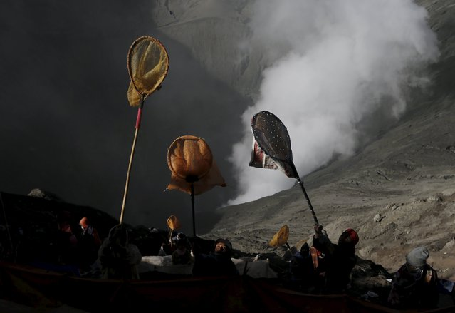 Villagers hold nets up into the air as they try to catch coins, thrown as offerings by Hindu worshippers into the crater during the Kasada Festival at Mount Bromo in Probolinggo, Indonesia's East Java province, August 1, 2015. (Photo by Reuters/Beawiharta)