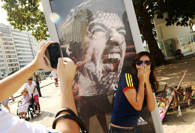 A woman takes a photo next to an advertisement featuring Uruguay's Luis Suarez, mocking the biting incident against opponent Giorgio Chiellini during the World Cup match against Italy, on Copacabana Beach on June 26, 2014 in Rio de Janeiro, Brazil. Suarez has been banned in today's ruling by FIFA for four months. (Photo by Mario Tama/Getty Images)